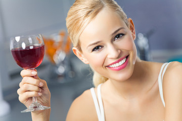 Portrait of young woman with glass of red wine