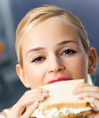 Woman eating sandwich, at home