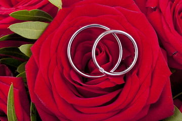 white gold wedding rings on a bridal bouquet with red roses