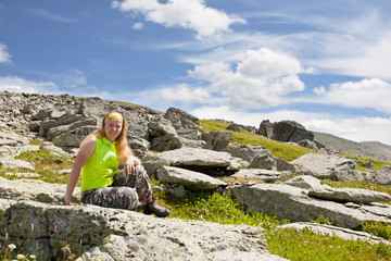 girl-tourist has a rest, sitting on stones