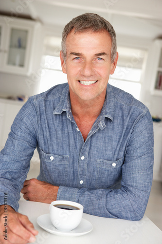 Mid age man with coffee at home