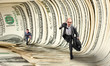Businessmen running in dollar tunnel