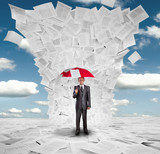 Businessman with red umbrella under huge wave of documents
