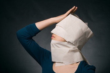 Young woman's head wrapped in paper.