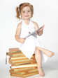 Cute little girl seated on books is playing with touchpad