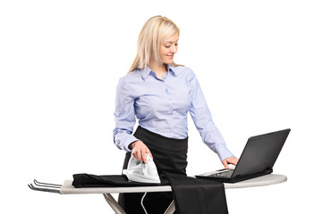 Businesswoman ironing his clothes and working on a laptop