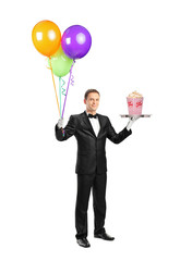 Butler carrying a tray with a popcorn box on it and balloons