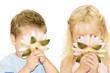 2 kleine Kinder riechen an einer Blüte