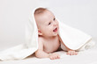 Cute baby smiling under white blanket
