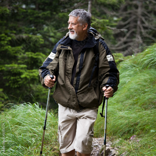 active handsome senior man nordic walking outdoors