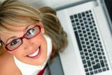 Vista superior de una atractiva joven frente a un portatil poster
