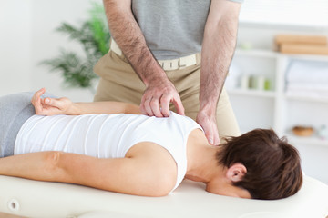 Masseur massaging a brunette woman's shoulder