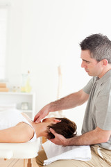 Chiropractor massaging a woman's neck