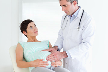 Doctor ausculating a pregnant woman's belly