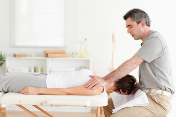 Masseur stretching a woman's head