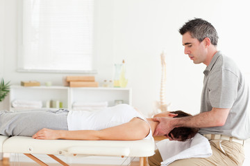 Chiropractor massaging woman's neck