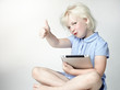 Cute little girl shows thump up for playing with touchpad