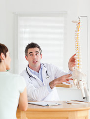 Male Doctor showing a female patient a part of a spine