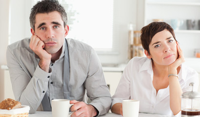 Worn out couple drinking coffee