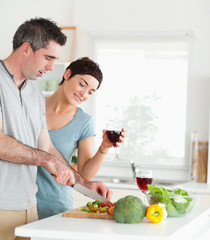 Handsome Man cutting vegetables while is woman is watching