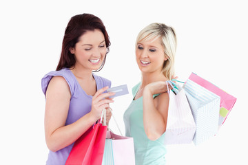 Cheerful women with shopping bags and a card