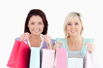Cheerful young women with shopping bags