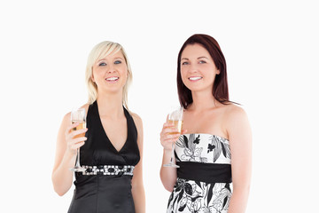 Smiling women in dresses drinking champaign