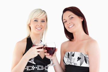 Joyful well-dressed women toasting with red wine
