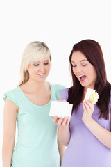 Blond young woman gifting her friend