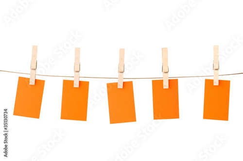 Blank pieces of paper and clothespins on white backgroun