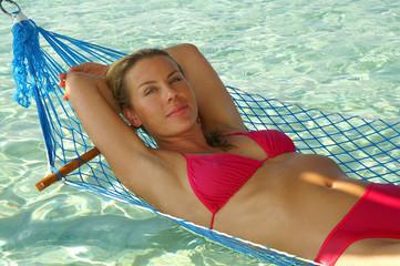 Junge Frau im Urlaub auf der Luftmatratze