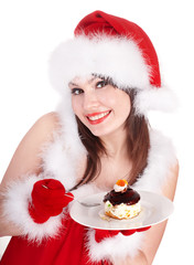 Christmas girl in santa hat and cake on plate.