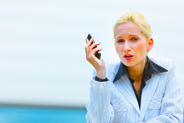 Outraged business woman with cell phone leaning on railing