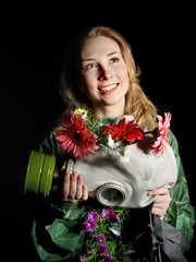 Woman holding flowers and gas mask .