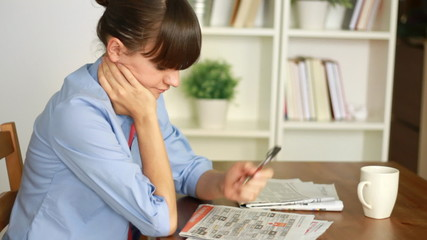 Young attractive woman looking in newspaper for job