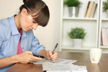 Woman looking for job with cellphone and newspaper