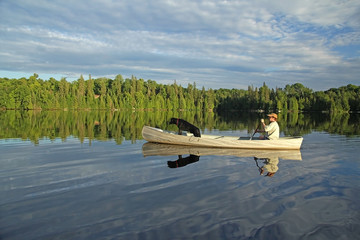 Canoeist with Dog in the Bow and Beautiful Reflection