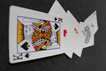 Cards on a black background - four Aces and a King