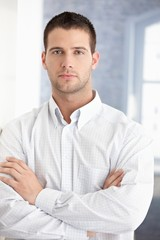 Young businessman standing arms crossed
