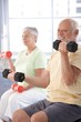 Elderly man exercising with dumbbells