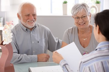 Senior couple at financial advisor smiling