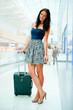 Portrait of young woman walking inside modern international airp