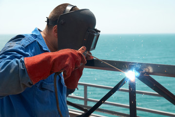 Welder working with metal construction