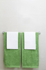 Green and white towels on a rail vertical