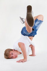 Teen b-boy standing on his head in freeze