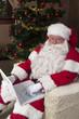 Modern Santa checking his list on his laptop