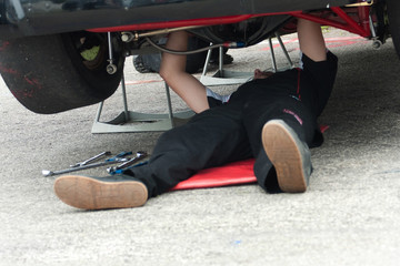 Mechanic underneath racing car