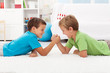 Boys arm wrestling in the kids room