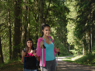 smiling girl in the forest with nordic walking poles