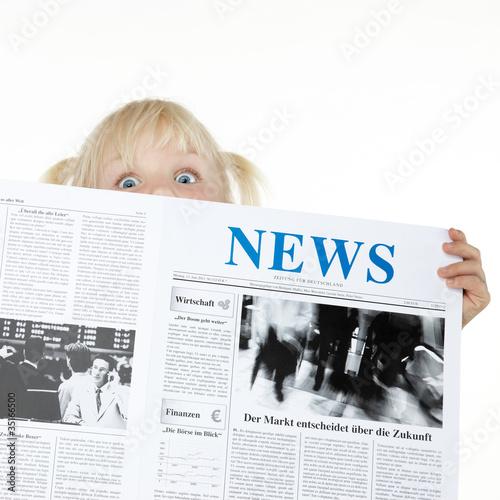 Leinwanddruck Bild Cute blond child is reading newspaper